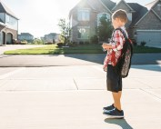 Young boy standing on concrete driveway
