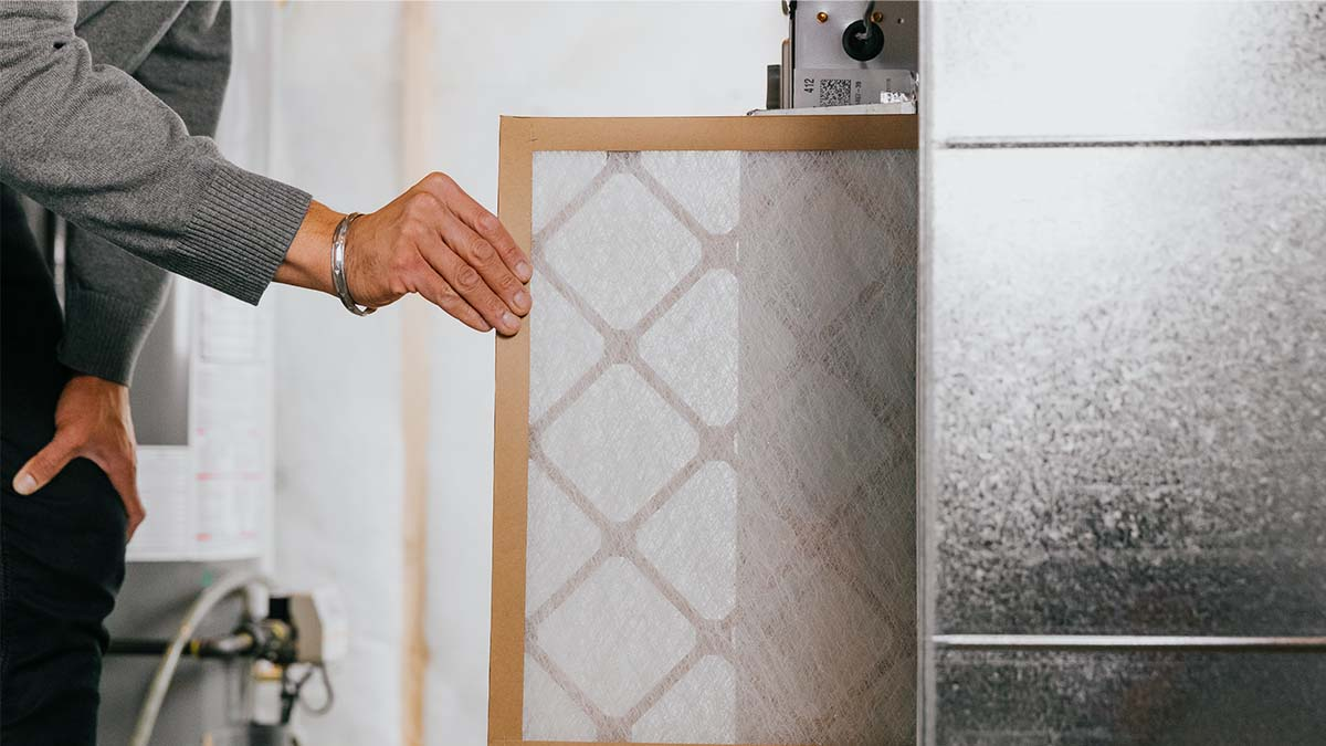 Closeup of mans hand pulling furnace filter out of furnace unit in electrical room