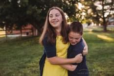 siblings embracing in a field