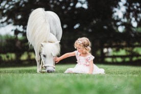 little girl wearing pink dress and floral crown sitting in the grass petting a white unicorn's head