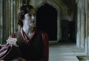 Captura de um frame da cena de Dumbledore e Minerva. A jovem Minerva olha na direção de Dumbledore, desconfiada, segurando pergaminhos.