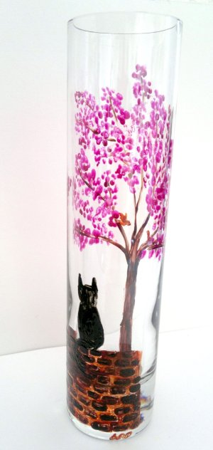Bud vase with a Spring tree with pinkblossom and a black cat on a wall