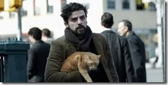 Llewelyn Davis tient un chat roux sous son bras dans une rue.