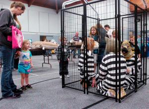 Kerri Hornback and her daughter, Vada, 3, look at children dressed as animals in jail Sunday during the Bail Me Out of the Shelter Pet Expo at Pritchard Community Center in Elizabethtown. Admission to the event was a bag of cat or dog food or cat litter. Photos courtesy Jill Picket, News Enterprise