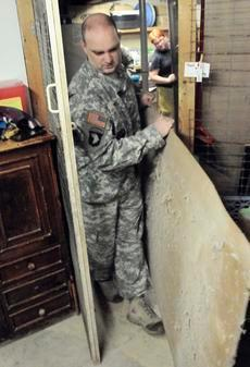 Staff Sgt. Jeffery Smith carries part of an old shelving unit out of the Animal Refuge Center Inc. laundry room for disposal Thursday morning. Smith and Sgt. James Oxley tore the old shelf out and assembled a new shelf with locking doors for animal medicine storage at the center.