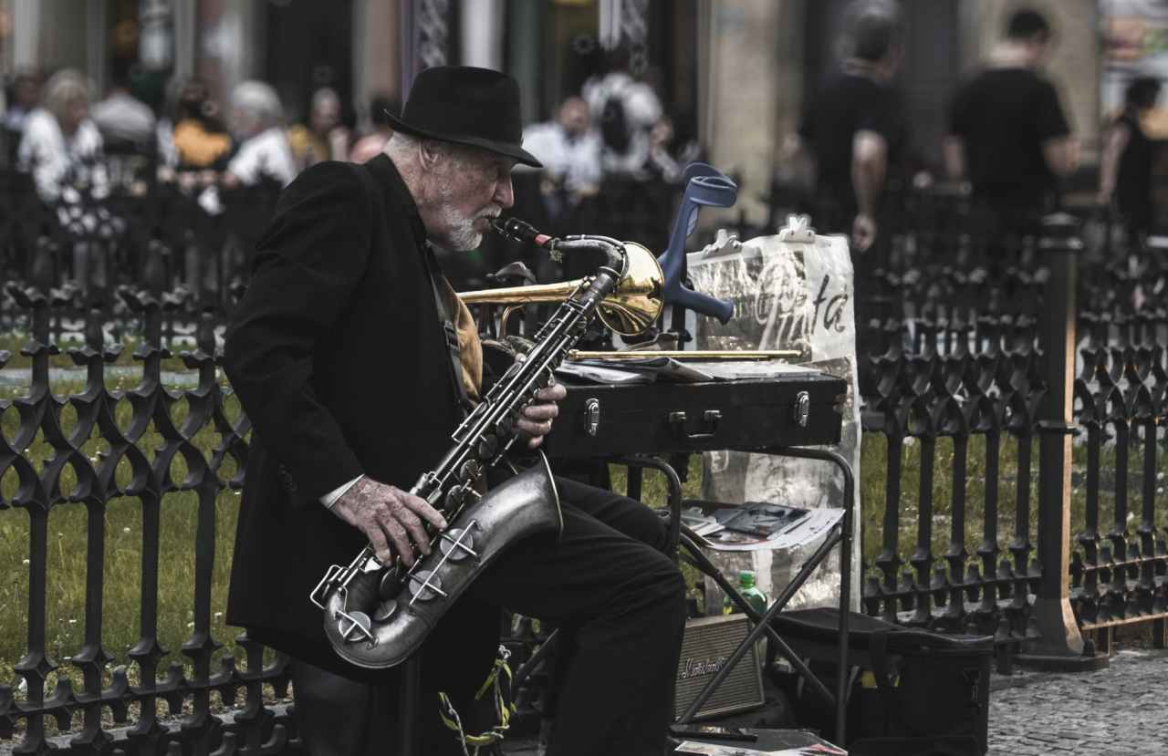 man sitting on stool while playing saxophone beside fence