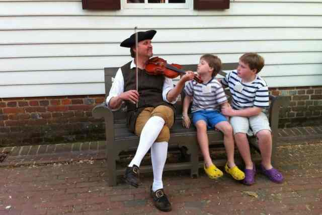 children listen to a historical reenactor play violin at Colonial Williamsburg Virginia