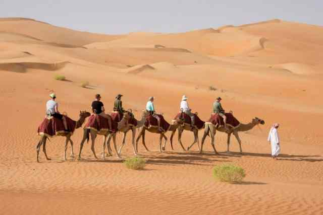 family riding camels in desert in UAE