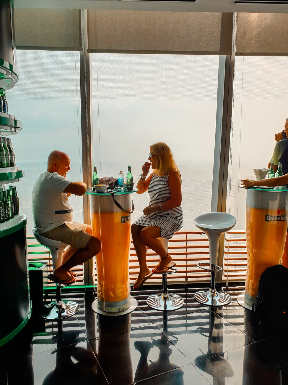 man and woman sitting on white bar stools