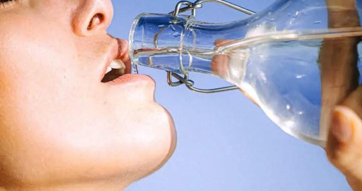 woman drinking water from glass bottle