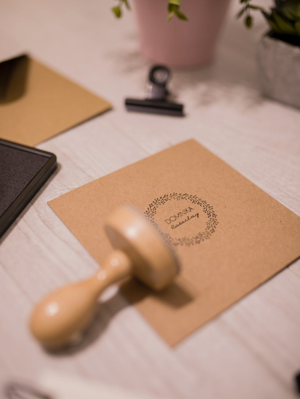 wooden stamp and invitation card on white table