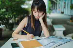 focused ethnic woman writing in copybook