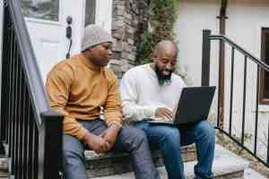 cheerful black businessman browsing laptop with son