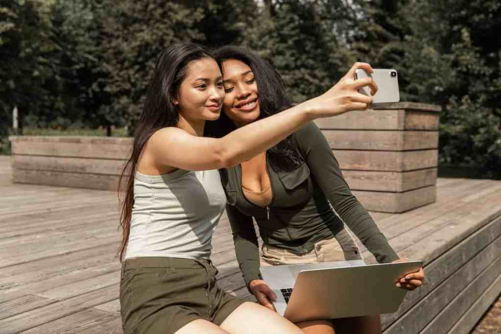 joyful young diverse girlfriends taking selfie on smartphone in park