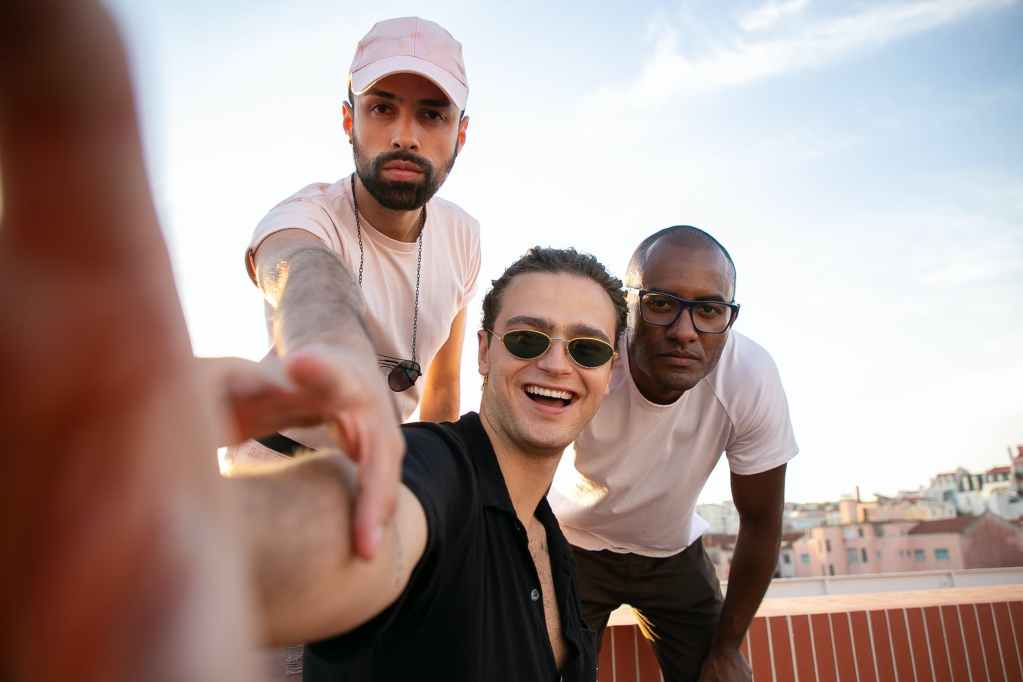 joyful trendy young diverse guys taking self portrait on roof
