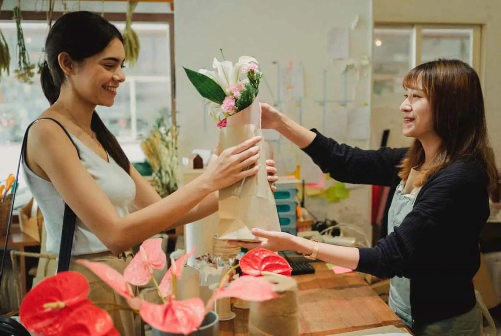 joyful woman receiving flowers from florist