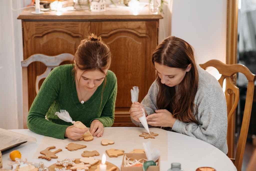 two young women putting icing on christmas cookies