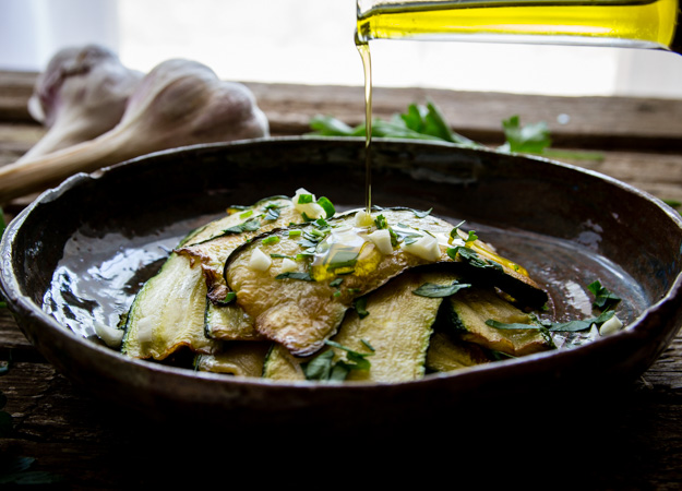 marinated zucchini in a bowl with parsley and chopped garlic, drizzling oil on top