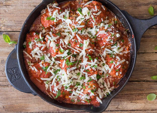 meatballs with shredded mozzarella in an iron skillet