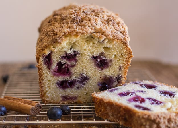 a slice cut from blueberry streusel loaf on a wire rack