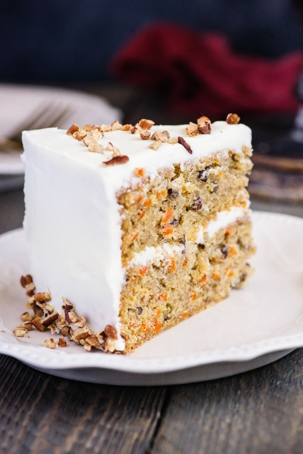 a slice of carrot cake on a white plate