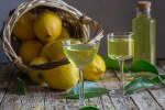 limoncello in two glasses with lemons in a basket