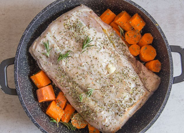 roast pork loin and carrots in a pot to be cooked