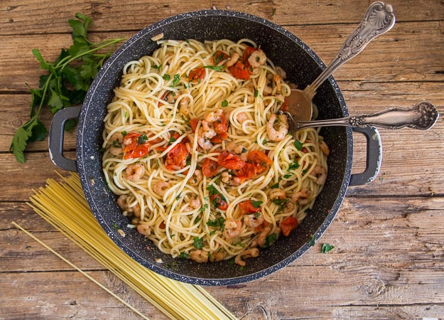 shrimp and tomato pasta cooked in a black pan