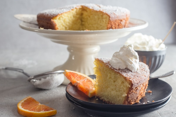 coconut orange cake with a slice on a black plate