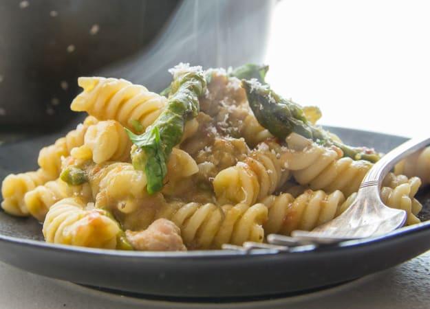 penne pasta with an asparagus cream sauce, cut up asparagus and Italian sausage on a black plate