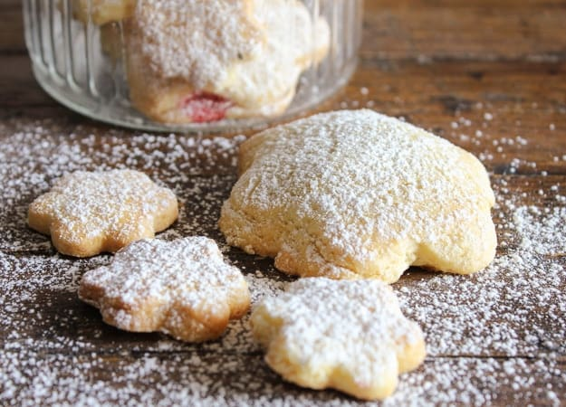 strawberry filled cookies on a wooden board sprinkled with powdered sugar