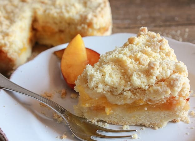 a slice of peach crumb cake on a white plate