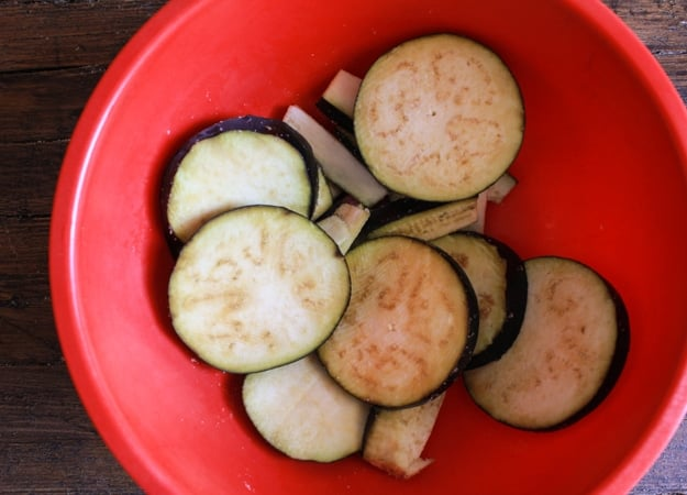 slices of eggplant in a red bowl