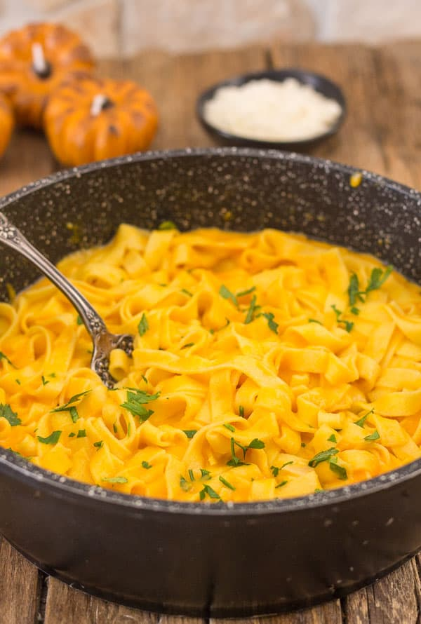 creamy pumpkin pasta sauce in a pot with a fork