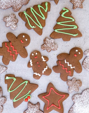 gingerbread cookies on a grey board, some decorated and some dusted with powdered sugar