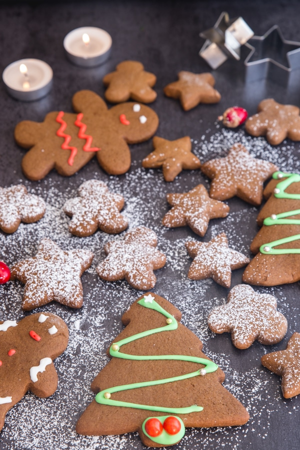 gingerbread cookies on a black board some decorated and some dusted with powdered sugar