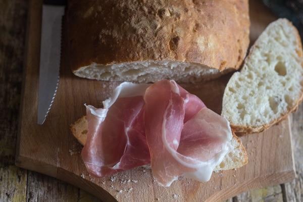 Ciabatta bread with prosciutto on top of a slice