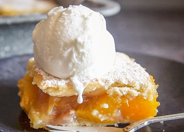 a slice of peach filled Italian crostata bars on a plate with a scoop of ice cream