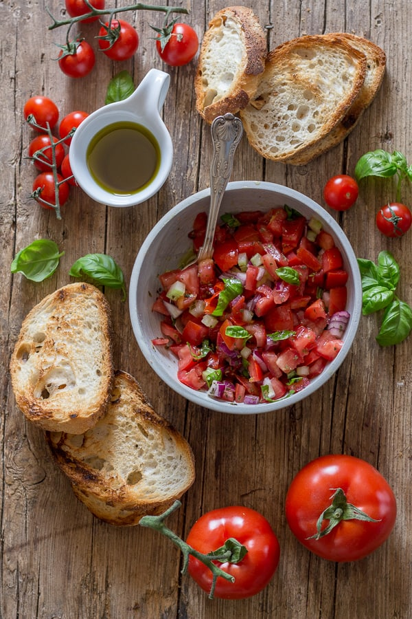 tomato bruschetta in a bowl and grilled bread on a board