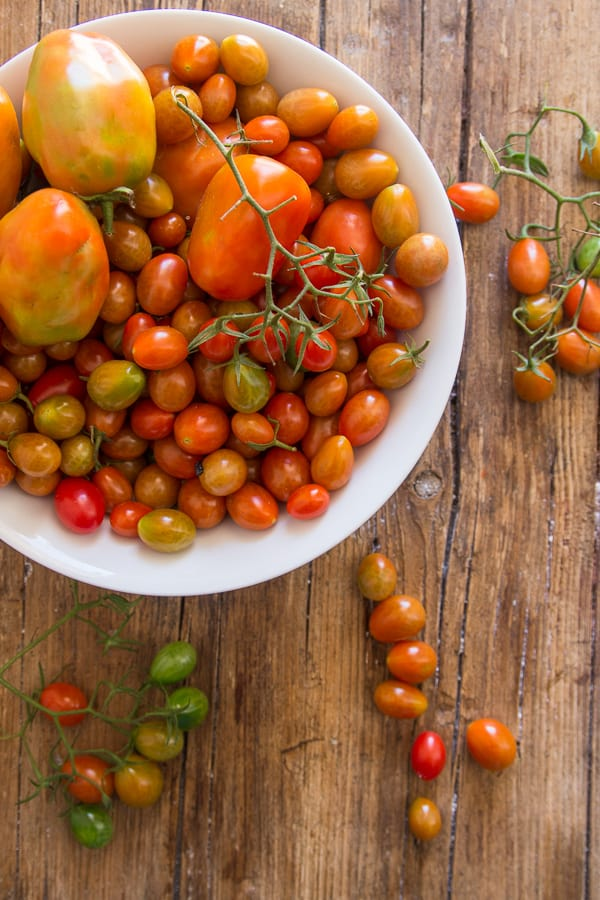 fresh tomatoes in a bowl and on a wooden board