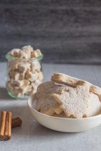 cinnamon sugar cookies in a bowl with 2 sticks of cinnamon beside it