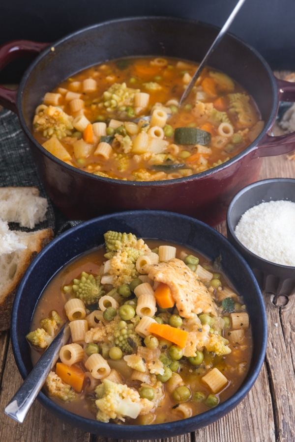 minestrone soup in a red pot and in a black bowl