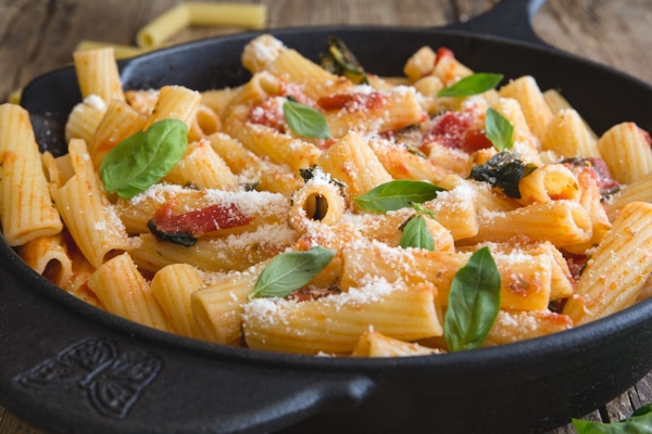 up close basil tomato sauce in a pan with rigatoni
