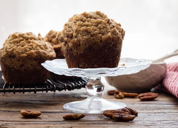 one banana crumb muffin on a small glass pedestal with 2 muffins in the background.