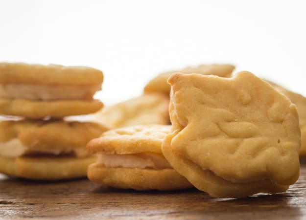 maple leaf sandwich cookies 2 stacked filled cookies, 1 on the board and single cookies in the background