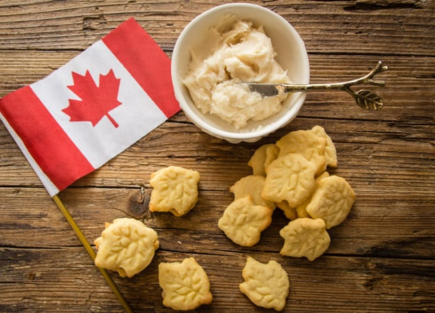 maple leaf sandwich cookies with Canadian flag and bowl of creamy maple filling