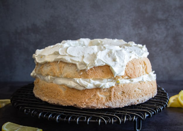 Lemon Tiramisu Cake filled and topped with a lemon mascarpone filling on a wire rack.