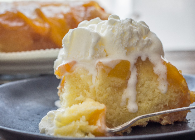 a slice of peach upside down cake on a plate with a scoop of ice cream on top.
