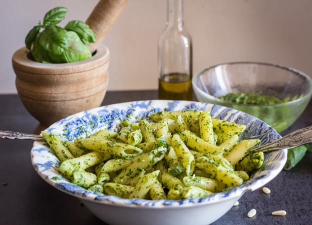a bowl of classic basil pesto with fresh basil, olive oil in the back ground