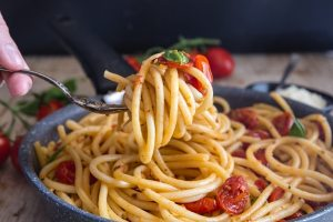 fork of roasted tomatoes and bucatini pasta